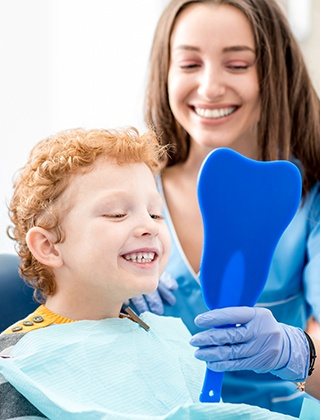 Little boy in dental chair looking at smile in mirror